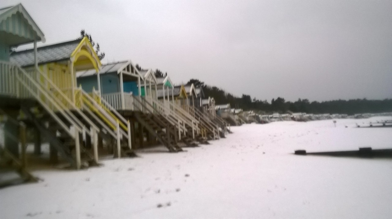 Beach covered in snow, snow on chalets, Wells-next-the-sea