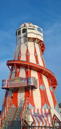 Orange and white vertical stripes on Helter Skelter on Clacton pier, bright blue sky behind.