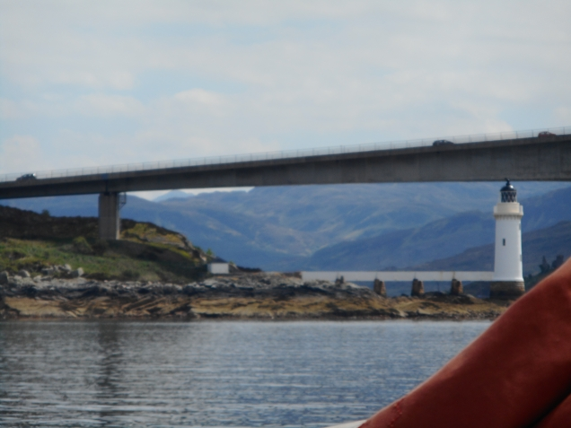 Skye lighthouse and road bridge viewed over a sail