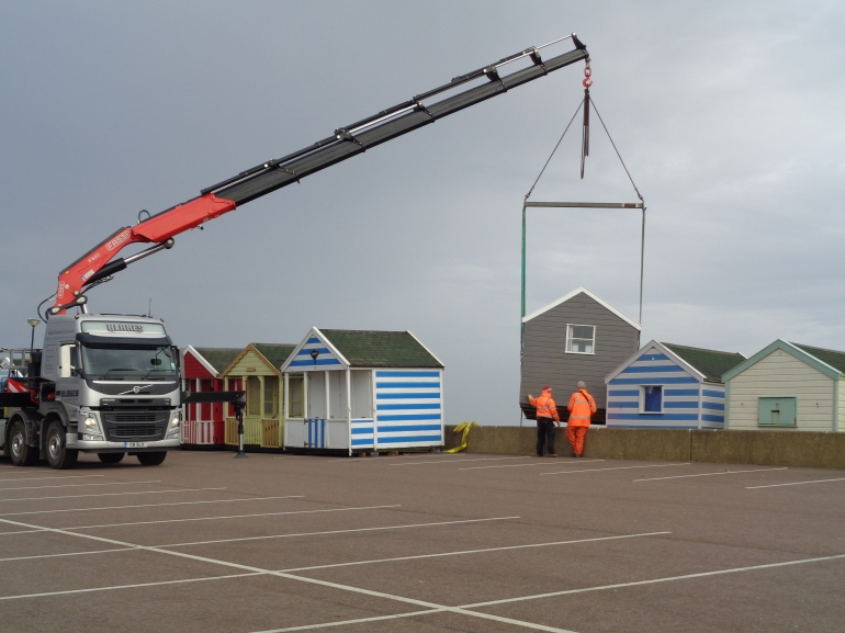 Southwold beach huts being lifted inside sea wall for the Winter